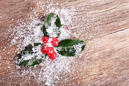 ilex aquifolium holly: European Holly (Ilex aquifolium) with berries on wooden background