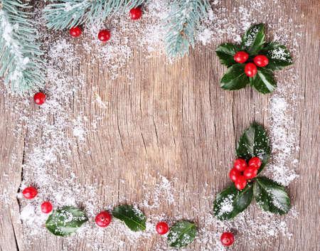 ilex aquifolium holly: Frame with European Holly (Ilex aquifolium) with berries on wooden background