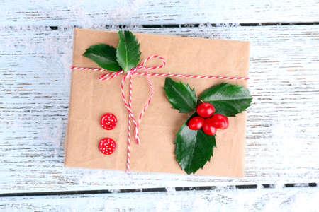 ilex aquifolium holly: Beautiful Cristmas gift with European Holly (Ilex aquifolium) on wooden background Stock Photo