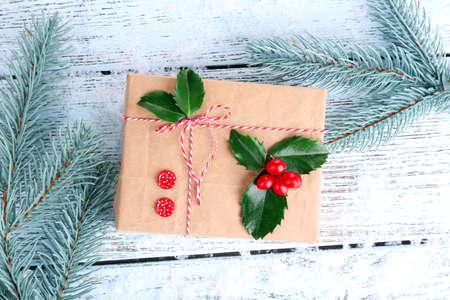 Beautiful Cristmas gift with European Holly (Ilex aquifolium) on wooden background photo