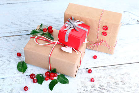 ilex aquifolium holly: Beautiful Cristmas gifts with European Holly (Ilex aquifolium) on wooden background