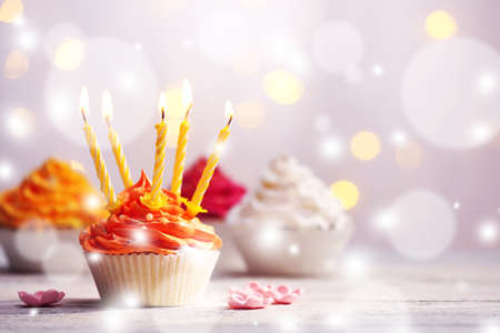 Delicious birthday cupcakes on table on light festive background