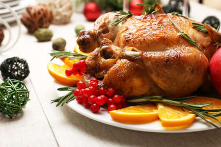 Baked chicken for festive dinner. Christmas table setting Stock Photo