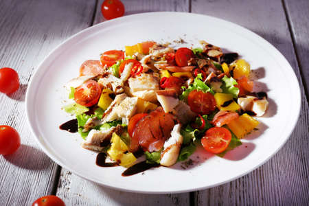 plato de pescado: Ensalada de pescado fresco con verduras en el plato sobre la mesa de madera de cerca