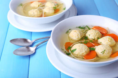 Soup with meatballs and noodles in bowls on color wooden background photo