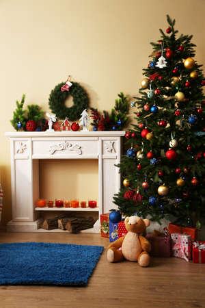 Beautiful Christmas interior with sofa, decorative fireplace and fir tree photo