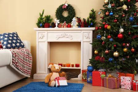 teddy wreath: Beautiful Christmas interior with sofa, decorative fireplace and fir tree Stock Photo