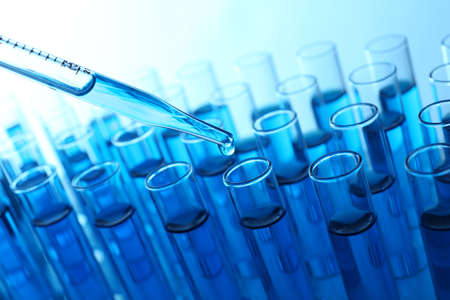 Pipette adding blue fluid to the one of test-tubes on light background Imagens