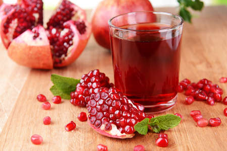 Ripe pomegranates with juice on table close-up