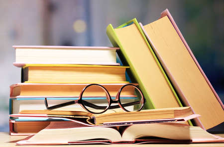 translation: Composition with glasses and books, on table, on light background Stock Photo