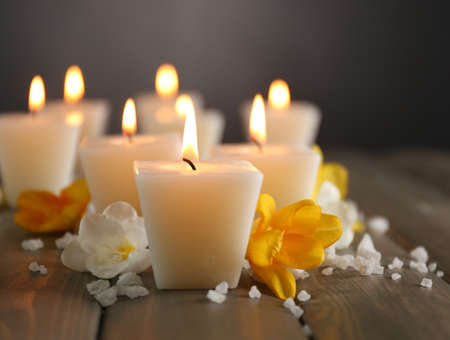 Beautiful candles with flowers on wooden background Stock Photo