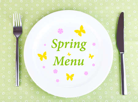 Plate with text Spring Menu, fork and knife on tablecloth background photo