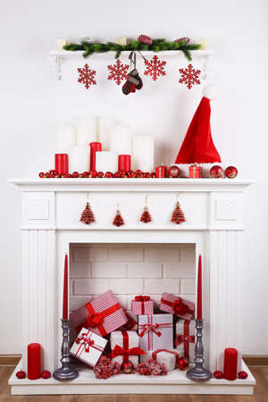 stone fireplace: Fireplace with Christmas boxes and candles on wooden floor
