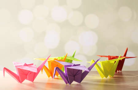 origami bird: Origami cranes on wooden table, on light background Stock Photo