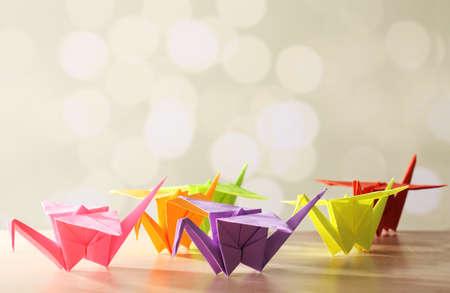 Origami kraanvogels op houten tafel, op lichte achtergrond