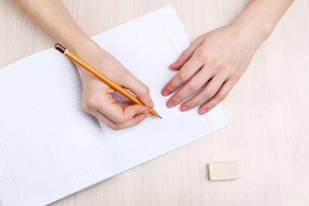 나무 테이블에 종이와 지우기 고무에 연필 쓰기와 인간의 손