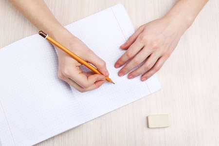 Human hands with pencil writing on paper and erase rubber on wooden table