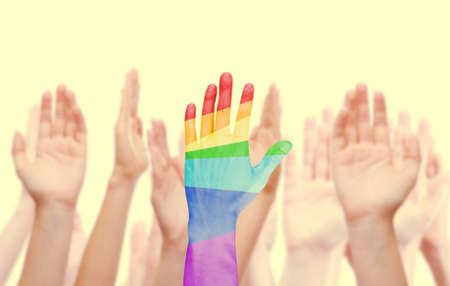 Man hands painted as the rainbow flag on other hands isolated on white photo