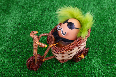 Egg riding bicycle on green background photo