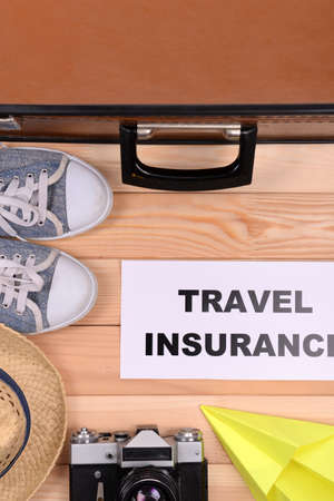 Suitcase and tourist stuff with inscription travel insurance on wooden background top view photo