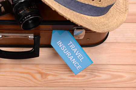insurer: Suitcase and tourist stuff with inscription travel insurance on wooden background