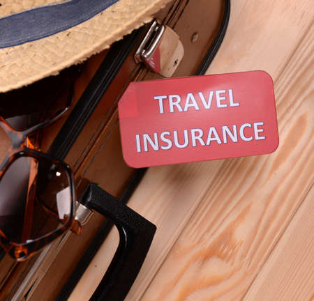 leather background: Suitcase and tourist stuff with inscription travel insurance on wooden background