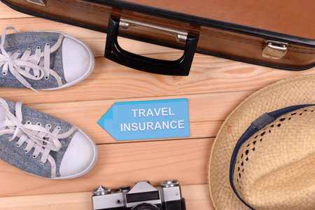 insurance: Suitcase and tourist stuff with inscription travel insurance on wooden background top view