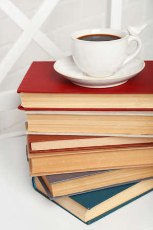 Pile of books with cup of hot drink on the chair on brick wall background photo