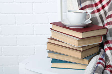 Pile of books with cup and plaid on the chair on brick wall background photo