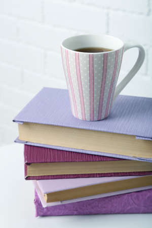Pile of books with cup on the chair on brick wall background photo