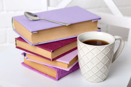 Pile of books with cup and spoon on the chair on brick wall background photo