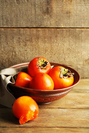 grange: Ripe sweet persimmons, on wooden table