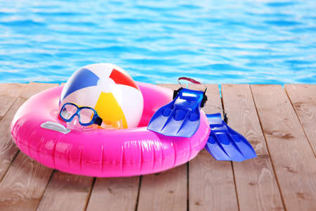 Bright beach accessories on pool background Imagens