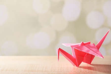 Origami crane on wooden table, on light background photo