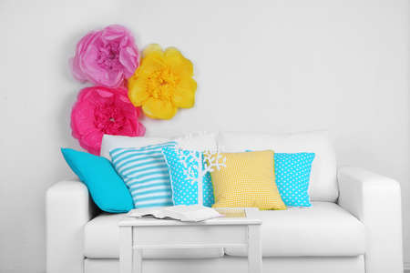 divan sofa: White sofa with colorful pillows in room on bright wall background
