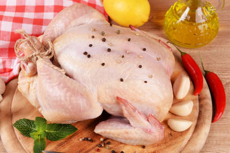 Raw chicken on wooden table photo