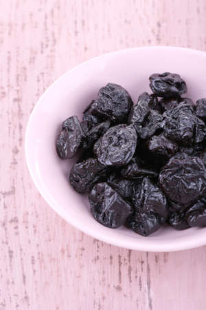 prunes: Bowl of prunes on color wooden background