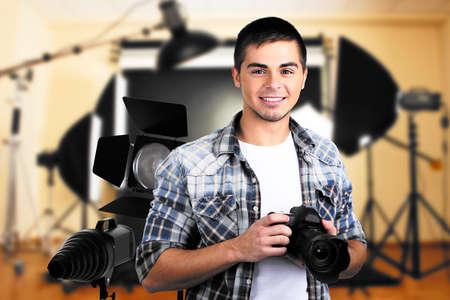 Jonge fotograaf met camera op de foto studio achtergrond Stockfoto
