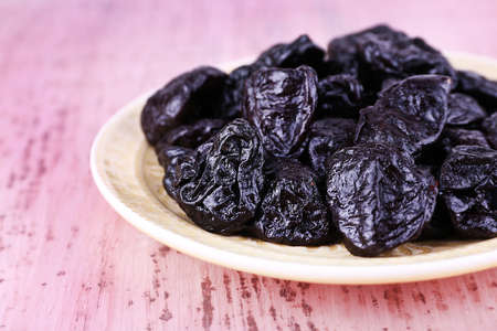 prunes: Plate with heap of prunes on color wooden background