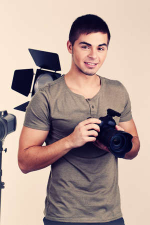 Young photographer with camera on photo studio background photo