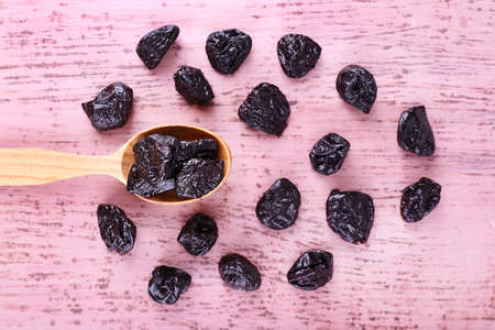 prunes: Spoon of prunes on color wooden background