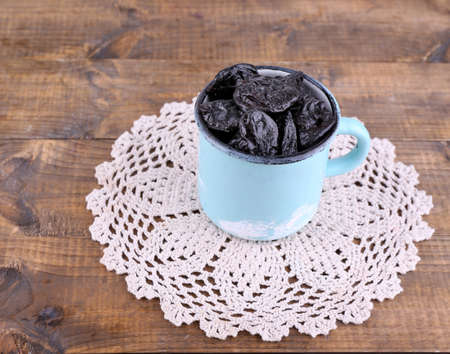 doily: Cup filled with prunes on lace doily, on wooden background Stock Photo