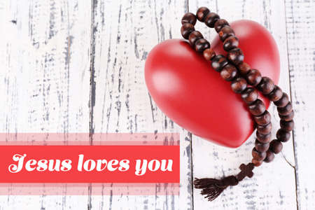 loves: Heart with rosary beads on wooden background and text Jesus loves you Stock Photo