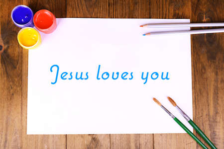 loves: Jesus loves you text on paper on wooden table background