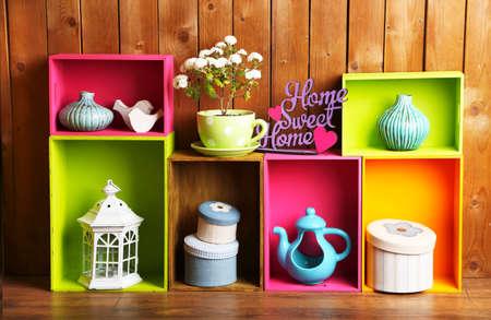 Mooie kleurrijke planken met verschillende huis verwante voorwerpen op houten muur achtergrond