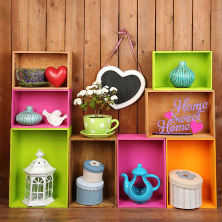 wooden furniture: Beautiful colorful shelves with different home related objects on wooden wall background Stock Photo