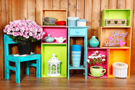 Beautiful colorful shelves with different home related objects on wooden wall background Фото со стока