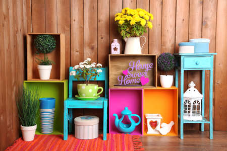 flower boxes: Beautiful colorful shelves with different home related objects on wooden wall background Stock Photo