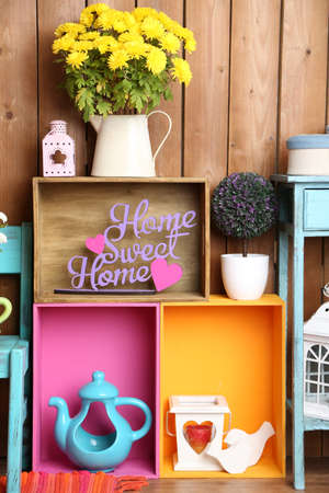 home related: Beautiful colorful shelves with different home related objects on wooden wall background Stock Photo