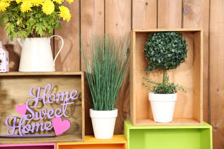 Beautiful colorful shelves with different home related objects on wooden wall background photo